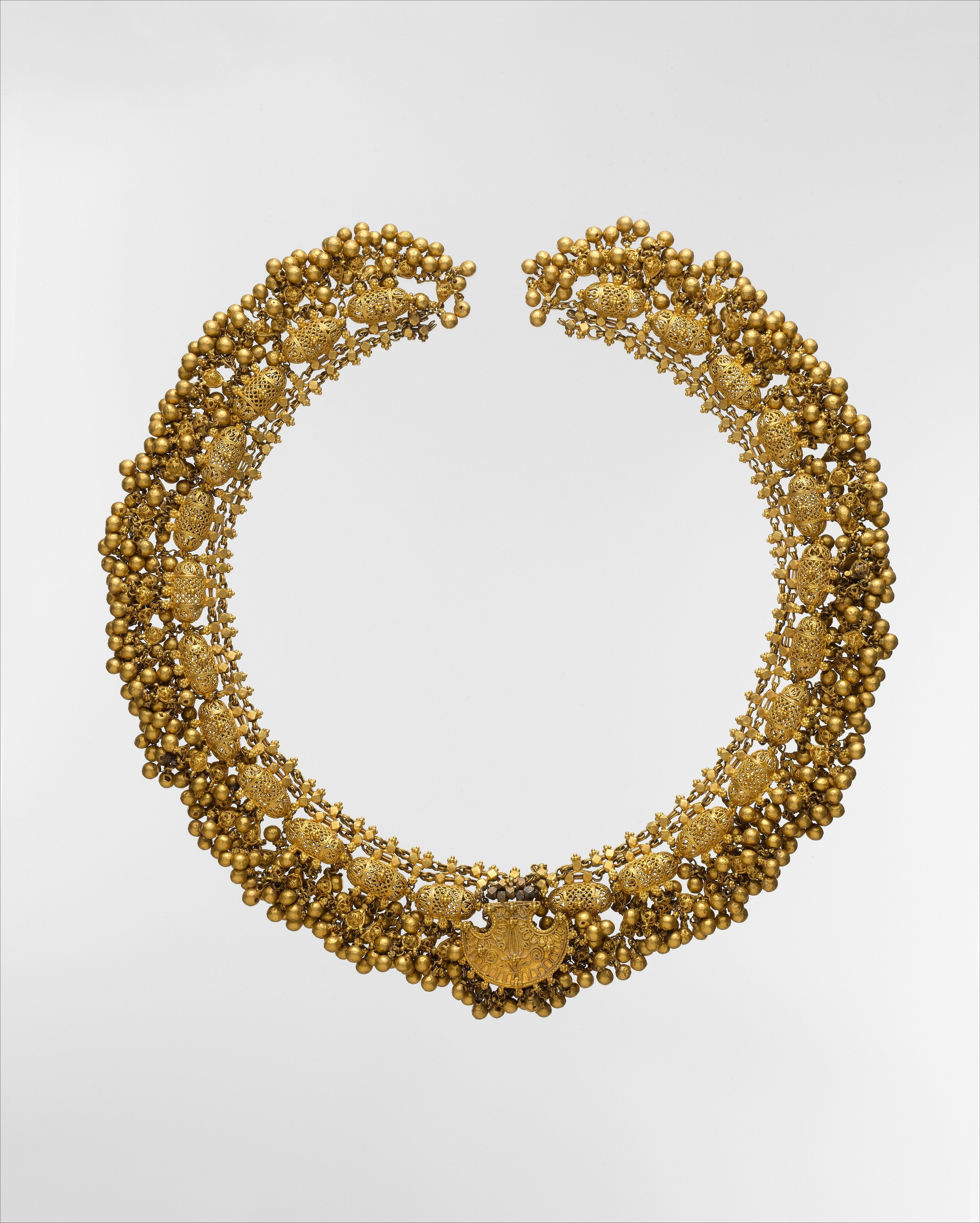 Necklace with Filigree and Beads, late 18th–early 19th century. The large fan-shaped pendant at the center of this necklace is decorated with flowers and scrolling motifs in gold. It is bordered by twelve finely filigreed amulets on either side, with clusters of small gold beads hanging below each. Together, these components form a substantial yet delicate piece of jewelry that would have been worn by a wealthy patron. Met Museum.