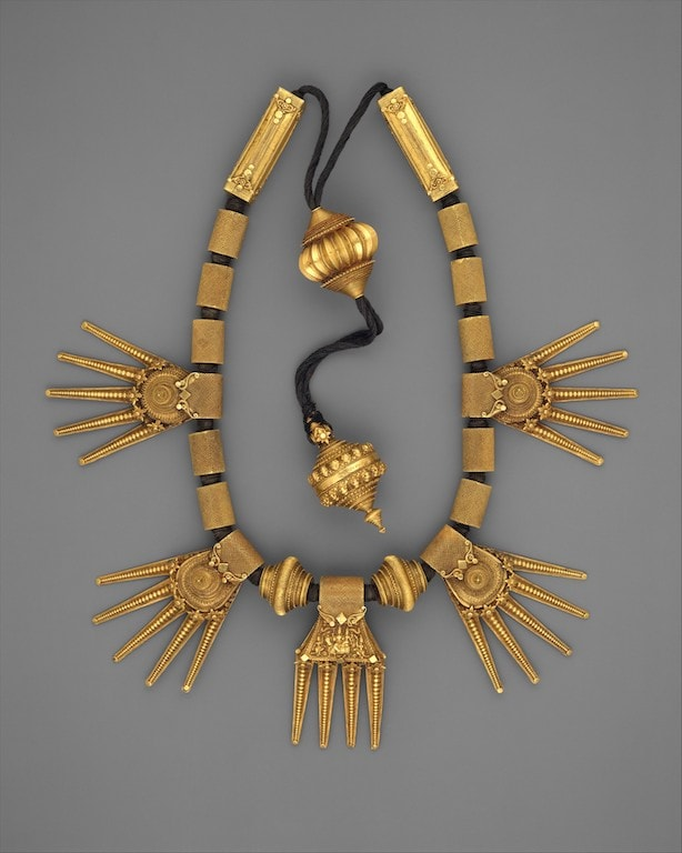 Chettiar marriage necklace. Kali-thiru. The elaborate Thali type, as seen here, generally includes a central Shiva and Parvati on a medallion. The four fingers of the central pendant are understood as denoting the four Vedas. 19th century. Met Museum.